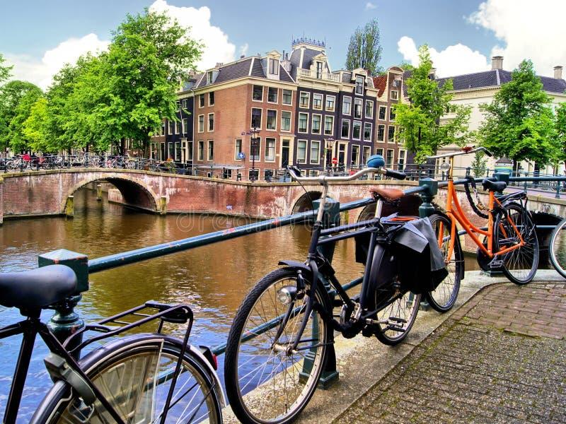Het kanaal en de fietsen van Amsterdam stock foto