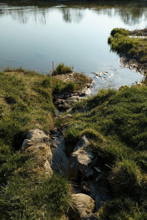 Het kanaal sluit zich aan bij een rivier in de stad Sabile, Letland royalty-vrije stock foto