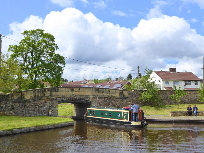 Het kanaal van de mensenleiding narrowboat onder brug royalty-vrije stock afbeelding