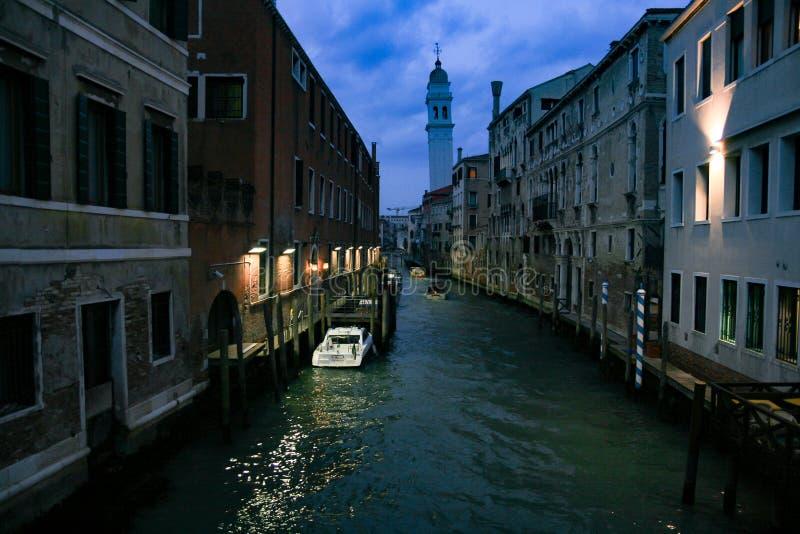 Het kanaal van Venetië bij nacht met straatlantaarn verlichtend huizen en kanaal stock foto's