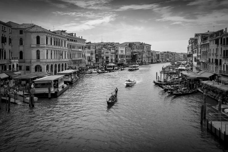 Het kanaal van Venetië en gondel en boten van de Rialto-Brug in zwart-wit stock fotografie