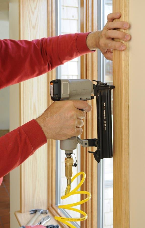 Het kanon dat van de spijker worden gebruikt om houten versiering om rond wi te installeren royalty-vrije stock afbeeldingen