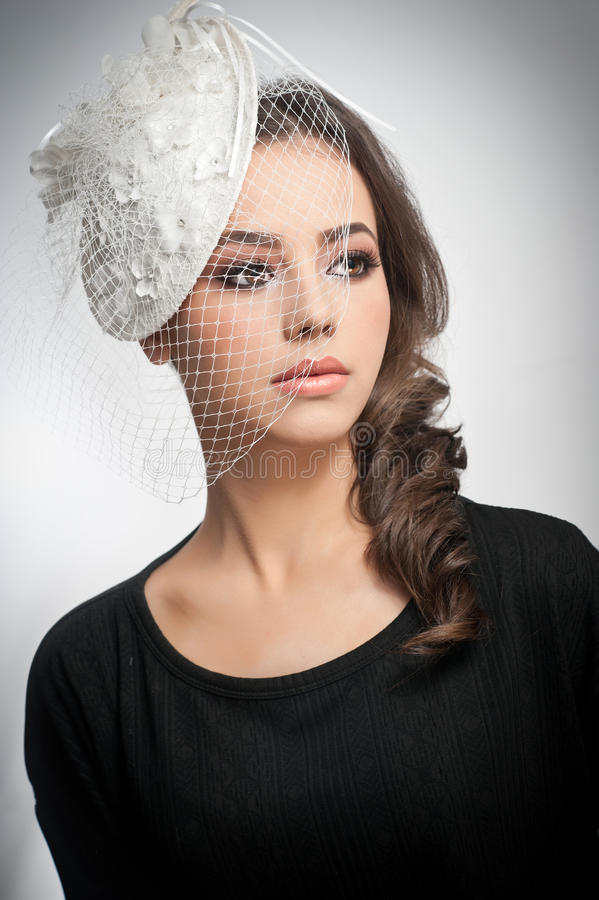 Het kapsel en maakt omhoog - het mooie jonge portret van de meisjeskunst Leuk brunette met wit GLB en sluier, studioschot Aantrek royalty-vrije stock foto