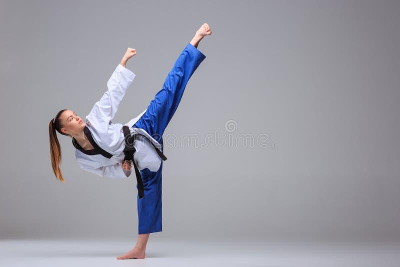 Het karatemeisje met zwart band stock foto