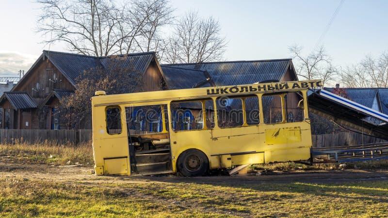 Het karkas van de schipbreukbus van gele schoolbus in stadsbinnenplaats stock foto