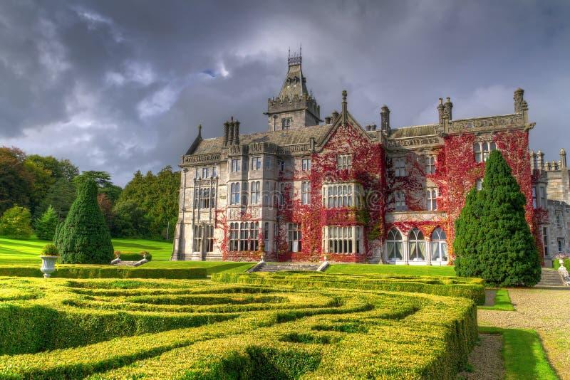 Het kasteel van Adare in rode klimop met tuinen stock foto