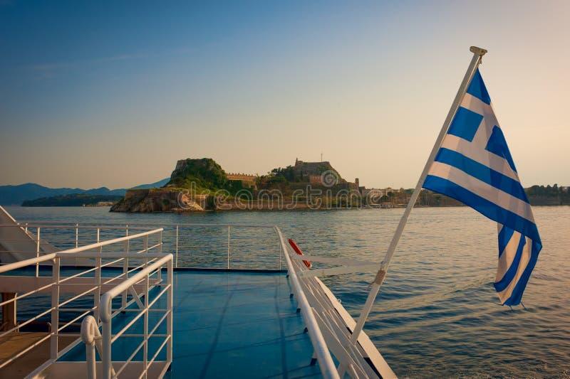Het kasteel van Korfu en Griekse die vlag in zonsondergang van een boot wordt voorgesteld stock fotografie