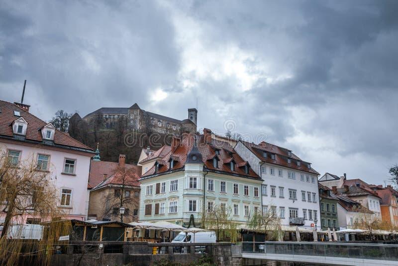 Het kasteel van Ljubljana tijdens een bewolkte regenachtige dag met de oude stad en de Ljubljanica-rivier in de voorgrond stock foto