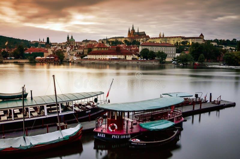 Het kasteelmening van Praag van de Vltava-rivierbank, boten vooraan, tijdens de schemer stock foto