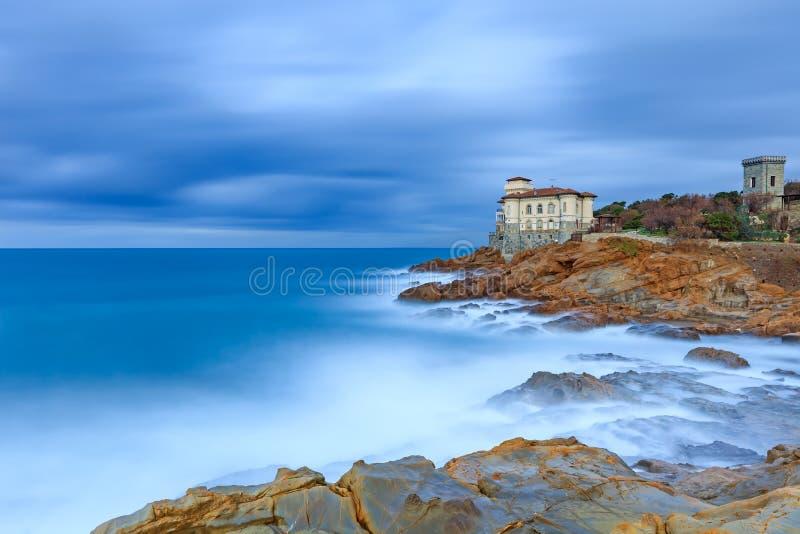 Het kasteeloriëntatiepunt van Boccale op klippenrots en overzees. Toscanië, Italië. Lange blootstellingsfotografie.
