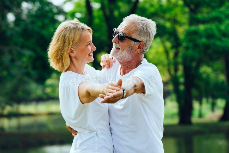 Het Kaukasische Bejaarde en vrouwen gelukkige glimlachen die in het park dansen royalty-vrije stock afbeelding