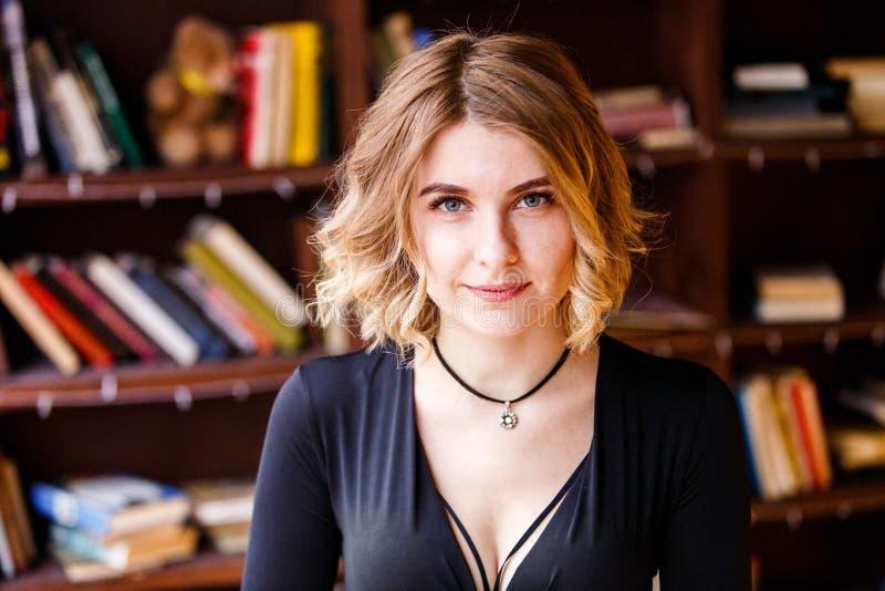 Het Kaukasische blonde vrouw stellen voor camera Kereltje die in het buitenland bestuderen Het concept van het onderwijs royalty-vrije stock fotografie