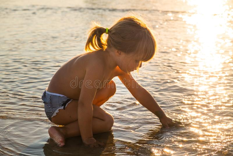 Het Kaukasische blondemeisje spelen met zand stock fotografie