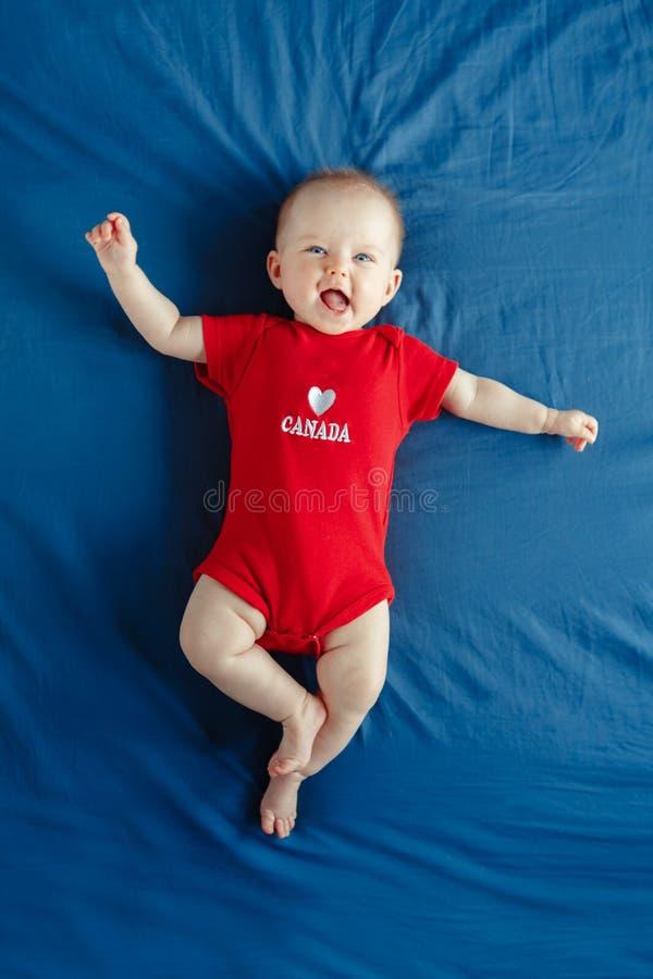 Het Kaukasische glimlachende meisje van de babyjongen met blauwe ogen die op bed thuis op de Dag van Canada liggen royalty-vrije stock foto's