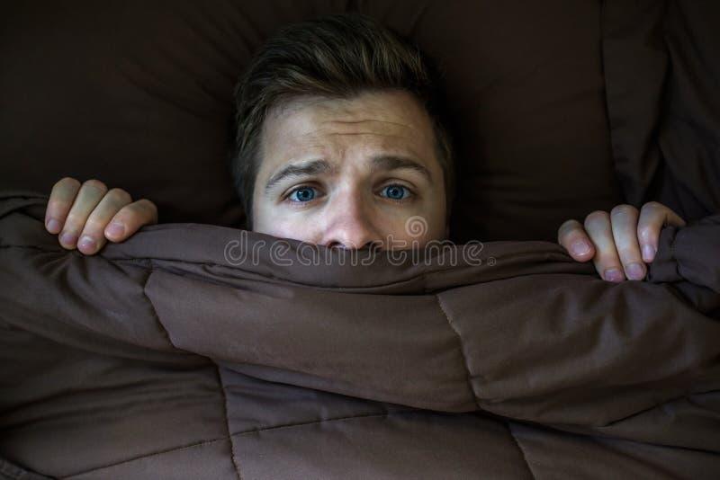 Het Kaukasische jonge mens verbergen in bed onder de deken thuis stock afbeeldingen