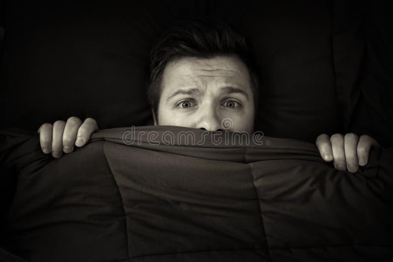 Het Kaukasische jonge mens verbergen in bed onder de deken thuis royalty-vrije stock foto's