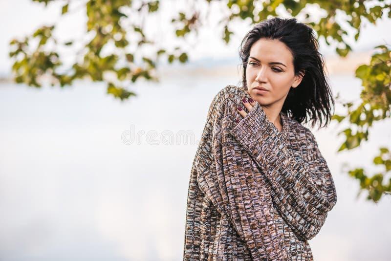 Het Kaukasische jonge vrouwelijke model voelt vrij, geniet vakantie van tijd, die tegen het meer stellen Het mooie vrouw stellen  royalty-vrije stock afbeelding