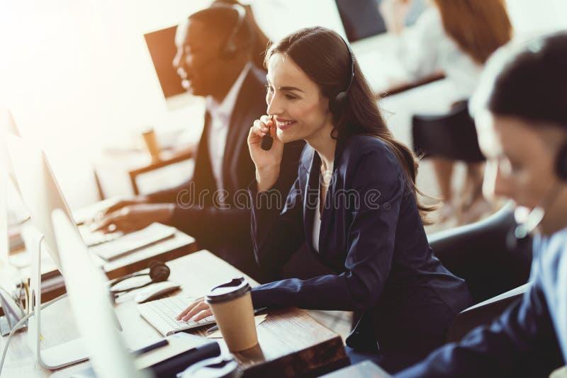 Het Kaukasische meisje bekijkt het werk in het call centre stock fotografie