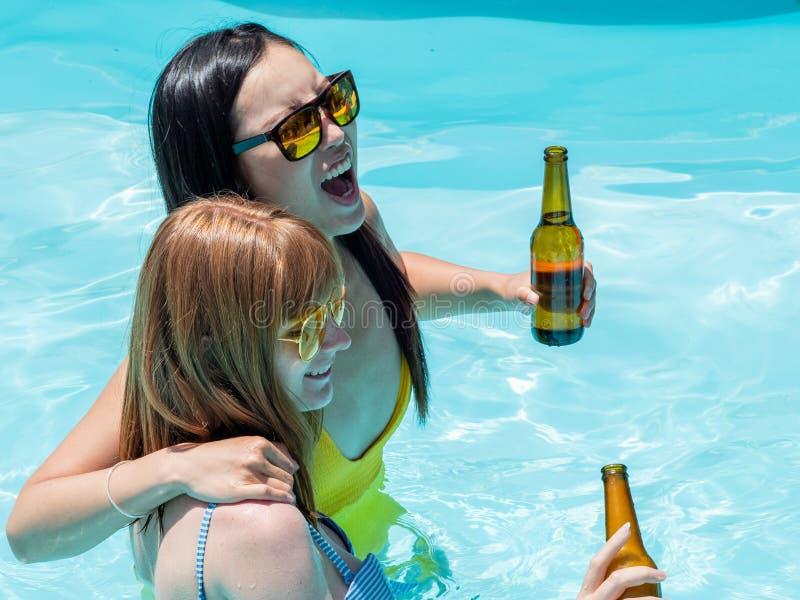 Het Kaukasische meisje en het oosterse meisje spelen en lachen in de pool, die bier drinken royalty-vrije stock fotografie