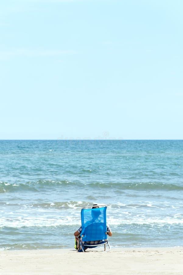 Het Kaukasische mens ontspannen op het strand stock foto
