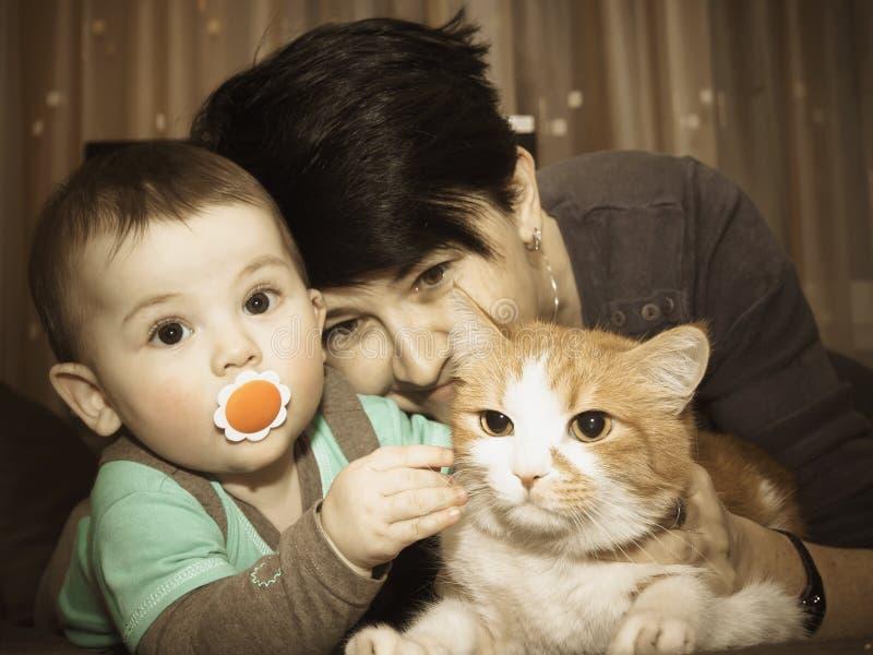 Het Kaukasische van de familiemoeder en baby spelen met kat stock foto's