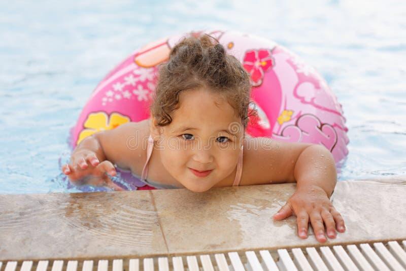 Het Kazakh meisje spelen dichtbij zwembad stock foto