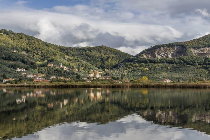 Het kenmerkende dorp van Massaciuccoli wordt weerspiegeld in de wateren van het homonymous meer, Luca, Toscanië, Italië stock afbeelding