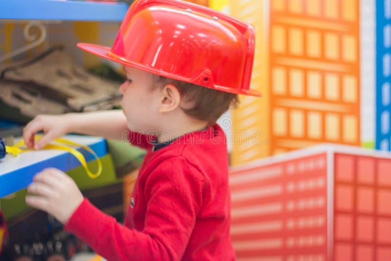 het kereltje bent jong mens die brandblusapparaat controleert stock foto's