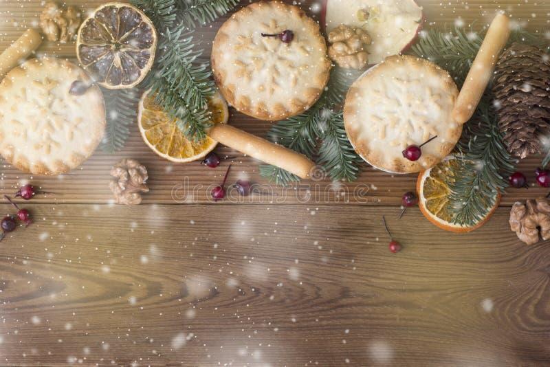 Het Kerstmisfruit hakt taartjes fijn De takken van de spar en de decoratie van Kerstmis Rustieke houten achtergrond stock afbeeldingen