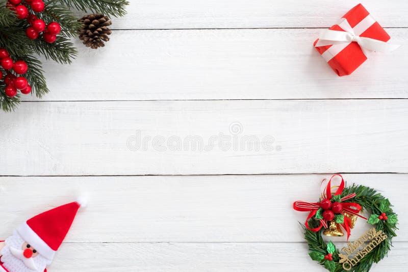Het Kerstmiskader van spar wordt gemaakt vertakt zich, hulstbes en rode giftdoos met decoratie op witte houten raad die stock fotografie