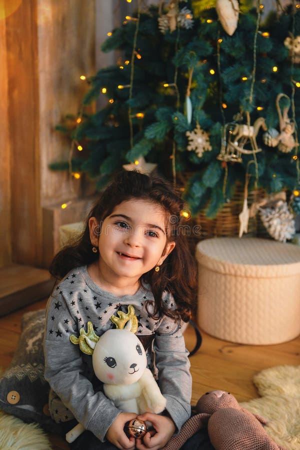 Het Kerstmisportret van gelukkige het glimlachen mooie meisjezitting op vloer met stelt onder de Kerstmisboom voor De wintervakan stock afbeelding