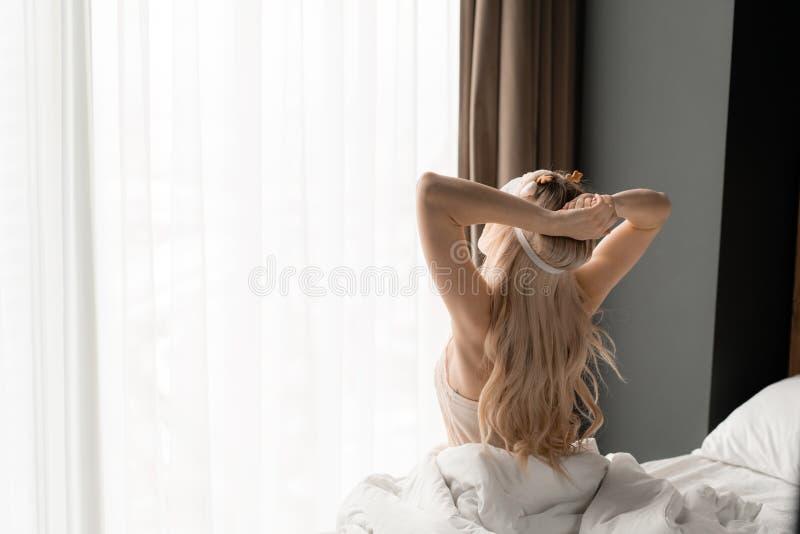 Het kielzog van de vrouw omhoog Ochtend in hotelruimte Zit op comfortabel bed in masker voor het slapen op hoofd Groot venster op royalty-vrije stock afbeelding