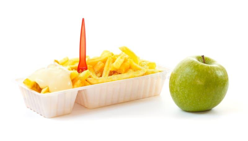 Het kiezen van een gezonde appel of een ongezond gedeelte Frieten stock fotografie