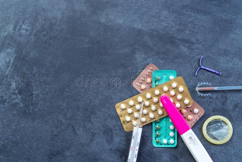 Het kiezen van methode van contraceptie: Geboortenbeperkingspillen, een injectiespuit, condoom, spiraaltje-Methode, op grijs royalty-vrije stock foto's