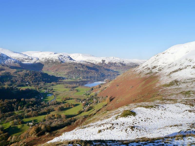 Het kijken aan Ullswater met het snow-capped bergen omringen stock foto's