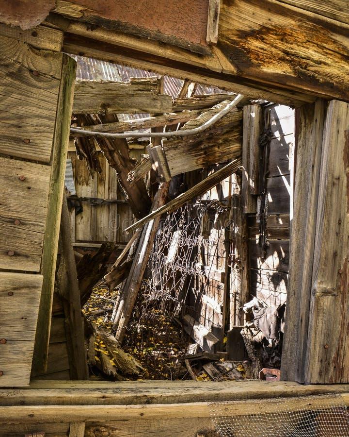 Het kijken binnen het Venster van een Verlaten Huis van de Wilde Westennen in Daling stock fotografie