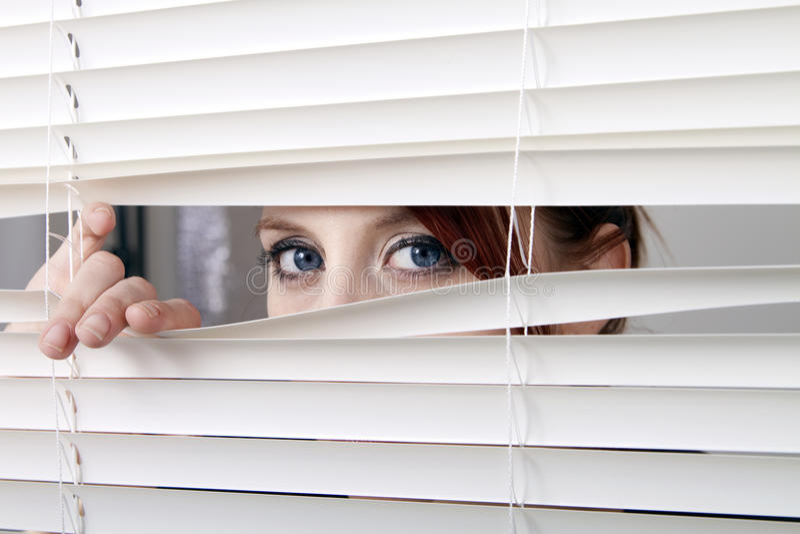 Het kijken door de vensterzonneblinden stock afbeeldingen