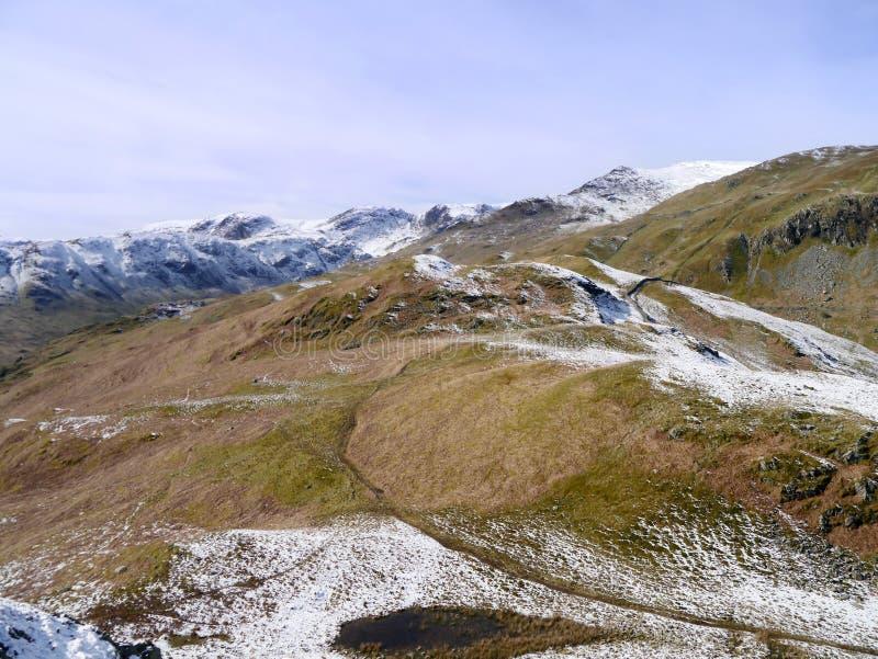 Het kijken neer aan weg met het omringen van snow-capped bergen stock foto
