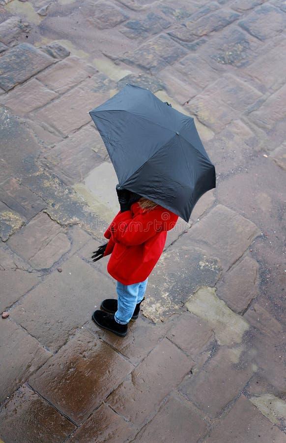 Het kijken neer op een vrouw die een paraplu op een natte dag gebruiken stock foto's