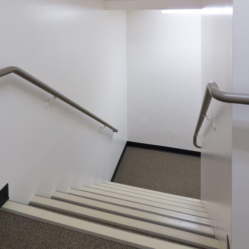 Het kijken onderaan een goed aangestoken trap met leuningen royalty-vrije stock afbeelding