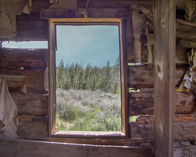 Het kijken uit van rustiek cabinevenster royalty-vrije stock fotografie