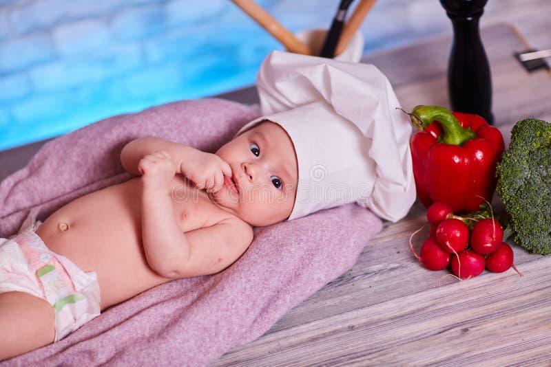 Het kind, babymeisje ligt op de keukenlijst in GLB van een chef-kok - naast hem zijn groenten, groene paprika, radijs, juiste bro royalty-vrije stock foto's