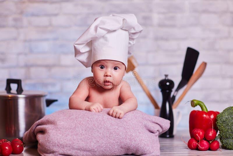 Het kind, babymeisje ligt op de keukenlijst in GLB van een chef-kok - naast hem zijn groenten, groene paprika, radijs, juiste bro stock afbeelding