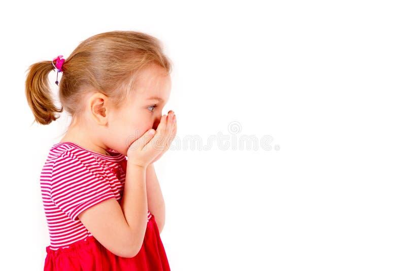 Het kind behandelt haar mond met handen stock foto
