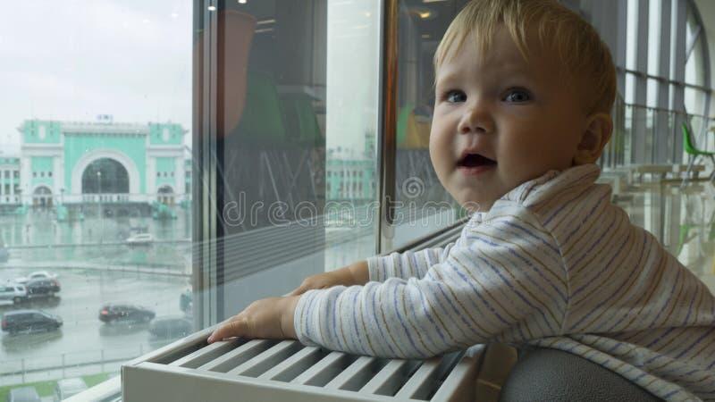 Het kind bekijkt uit het venster de stad royalty-vrije stock foto's