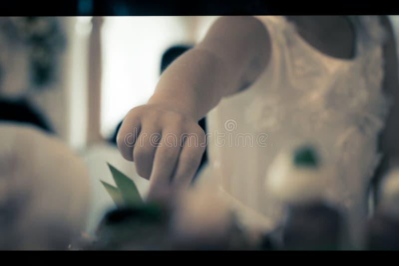 Het kind bereikt voor het voedsel van de lijst, kunt u de uitgestrekte hand zien stock afbeelding