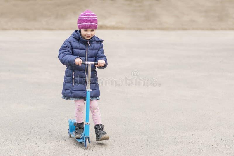 Het kind berijdt een autoped op asfalt royalty-vrije stock fotografie