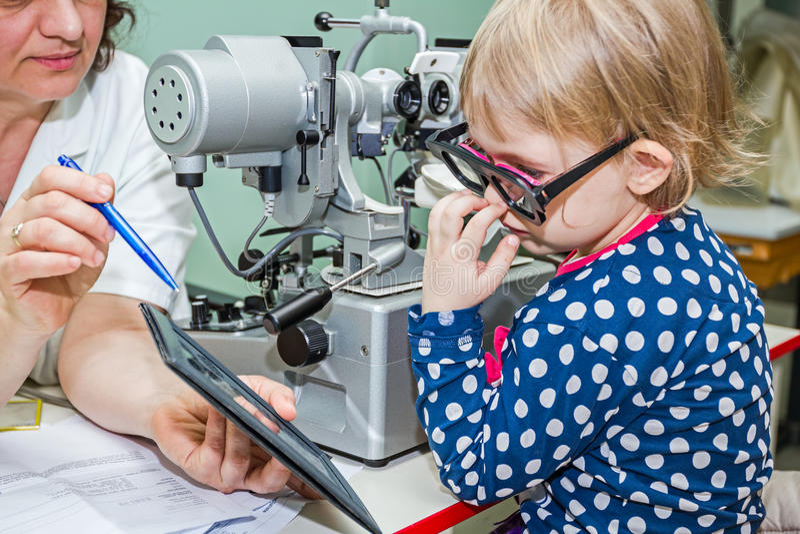 Het kind is bij oogonderzoek in kliniek met speciaal materiaal stock afbeeldingen