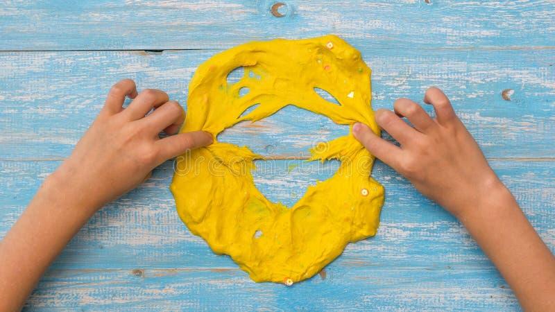 Het kind breekt het gezicht van een geel slijm op een houten lijst stock afbeelding
