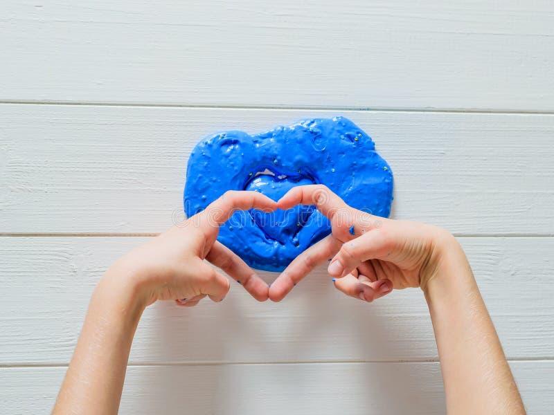 Het kind buigt zijn vingers in de vorm van een hart op een blauw slijm royalty-vrije stock foto's